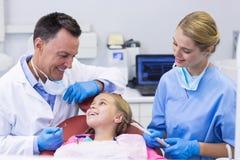 Dentista ed infermiere che interagiscono con un giovane paziente Fotografie Stock