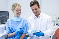 Dentista ed infermiere felici che per mezzo della compressa digitale Immagini Stock Libere da Diritti