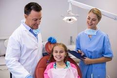 Dentista ed infermiere femminile che stanno accanto al giovane paziente Fotografie Stock Libere da Diritti
