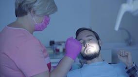 Dentista em condições de verificação médicas da máscara e das luvas de seu paciente que usa gestos Doutor profissional f?mea vídeos de arquivo