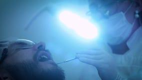 Dentista en el trabajo en la oficina Un doctor de sexo femenino examina los dientes y los mandíbulas de un paciente masculino metrajes