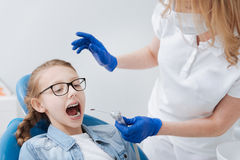 Dentista entrenado profesional que aplica las nuevas herramientas dentales Foto de archivo libre de regalías