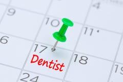 Dentista escrito en un calendario con un perno verde del empuje para recordar y imágenes de archivo libres de regalías