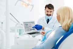 Dentista especializado que consulta o paciente imagem de stock