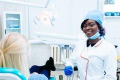 Dentista fêmea afro-americano que trata o paciente na clínica Conceito dental da clínica imagem de stock royalty free