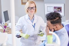 Dentista fêmea amigável Listening ao paciente foto de stock royalty free
