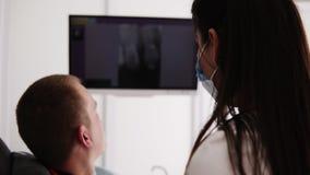 Dentista fêmea caucasiano que explica a imagem do raio X na tela ao paciente masculino Mostra a imagem do dente insalubre à video estoque
