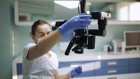 Dentista fêmea com ferramentas dentais - microscópio, espelho e ponta de prova tratando os dentes pacientes no escritório dental  filme