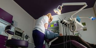 Dentista fêmea com ferramentas dentais que verifica acima dos dentes pacientes imagens de stock