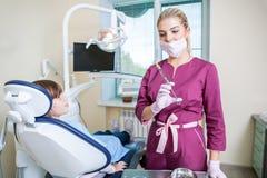 Dentista fêmea no escritório dental que fala com paciente fêmea e que prepara-se para o tratamento imagem de stock royalty free
