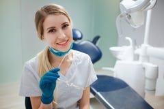 Dentista fêmea novo alegre para sentar-se na sala e na pose à câmera Sorri O doutor guarda vidros à disposição imagens de stock royalty free