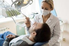 Dentista fêmea novo Treating Patient foto de stock