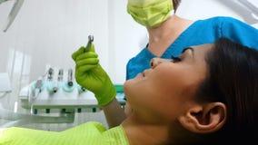 Dentista fêmea que prepara-se para furar pacientes para abaixar os dentes do pré-molar, serviços dentais fotografia de stock royalty free