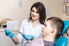 Dentista f?mea novo e seu paciente que ciao aos dentes imagens de stock royalty free