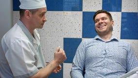Dentista feliz y paciente que comunican después de tratamientos Imagen de archivo libre de regalías
