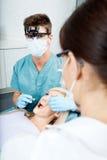 Dentista And Female Assistant que trata a un paciente en foto de archivo
