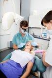 Dentista And Female Assistant que trata a un paciente en imagen de archivo libre de regalías