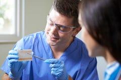 Dentista Giving Woman Advice sui denti cosmetici che imbianca immagini stock libere da diritti