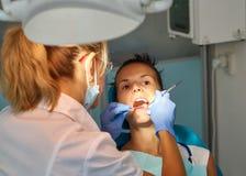 Dentista hermoso de la mujer que trata un patient& x27; dientes de s en oficina dental imagen de archivo libre de regalías
