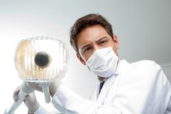 Dentista Holding Dental Lamp Immagine Stock