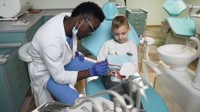 Dentista maschio africano che usando il modello di plastica dei denti per che insegna a poco paziente maschio a come utilizzare s archivi video