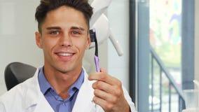 Dentista maschio attraente che sorride tenendo uno spazzolino da denti stock footage