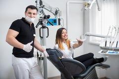 Dentista maschio bello con il paziente femminile attraente dopo il trattamento in clinica dentaria moderna fotografia stock libera da diritti