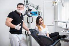 Dentista maschio bello con il paziente femminile attraente in ufficio dentario moderno fotografia stock libera da diritti