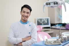 Dentista maschio che attraversa la clinica dentaria di Armin immagine stock