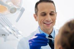 Dentista maschio positivo che lavora con un paziente fotografia stock libera da diritti