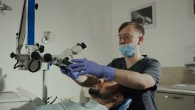 Dentista masculino com as ferramentas dentais na clínica - microscópio, espelho e ponta de prova tratando os dentes pacientes no  filme