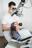 Dentista masculino com ferramentas dentais - microscópio, espelho e ponta de prova tratando os dentes pacientes no escritório den imagens de stock royalty free