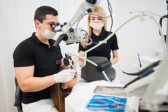 Dentista masculino e assistente fêmea que tratam os dentes pacientes com as ferramentas dentais - microscópio, espelho e broca imagem de stock