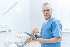 Dentista na escrita uniforme na prancheta na clínica dental com paciente atrás Fotografia de Stock Royalty Free