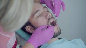 Dentista na máscara médica e luvas que verificam a boca do paciente que usa ferramentas médicas Doutor profissional f?mea video estoque