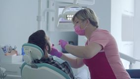 Dentista na máscara médica e luvas que verificam a boca do paciente que usa ferramentas médicas em um escritório dental moderno vídeos de arquivo