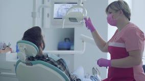 Dentista na máscara médica e luvas que verificam a boca do paciente que usa ferramentas médicas em um escritório dental moderno video estoque