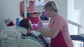 Dentista na máscara médica e luvas que verificam a boca do paciente que usa um espelho Assistente que traz o instrumento video estoque