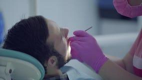 Dentista na máscara médica e luvas que verificam os tooths do paciente que usa ferramentas médicas Doutor profissional f?mea video estoque