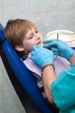 Dentista nella stanza dell'esame con il ragazzo in presidenza immagini stock