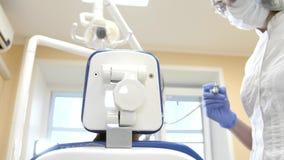 Dentista no trabalho na unidade dental com um cliente de encontro da menina Ponto de vista paciente video estoque