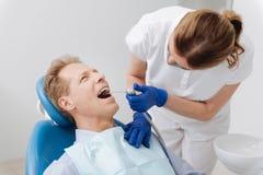 Dentista ordinato delicato che realizza manipolazione dentaria Fotografie Stock