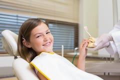 Dentista pediátrico que muestra el modelo de los dientes de la niña Foto de archivo libre de regalías