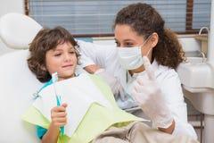 Dentista pediátrico que muestra a niño pequeño en silla el toothrbrush Fotografía de archivo