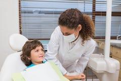 Dentista pediátrico que sonríe abajo en el niño pequeño en silla Imagenes de archivo