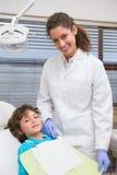 Dentista pediátrico que sonríe con el niño pequeño en la silla Foto de archivo libre de regalías