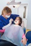 Dentista pediatrico che esamina il suo giovane paziente Immagini Stock