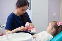 Dentista pediatrico che istruisce una bambina sorridente circa la dente-spazzolatura adeguata, dimostrante su un modello presto Immagine Stock Libera da Diritti