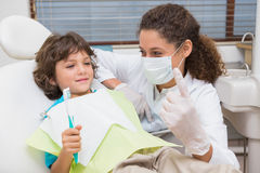 Dentista pediatrico che mostra a ragazzino nella sedia il toothrbrush Fotografia Stock