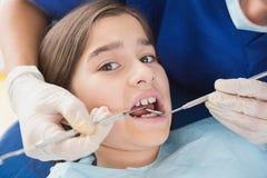 Dentista pediatrico che per mezzo dell'esploratore dentario e dello specchio ad angolo Fotografia Stock Libera da Diritti